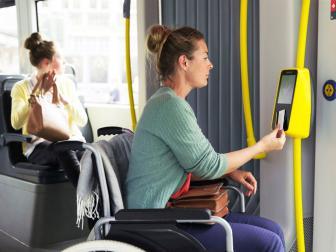 Rolstoelgebruiker scant de mobib-kaart op de bus