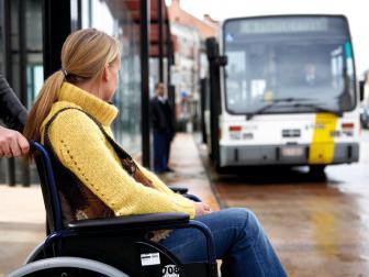 rolstoelgebruiker wacht op de aankomende bus
